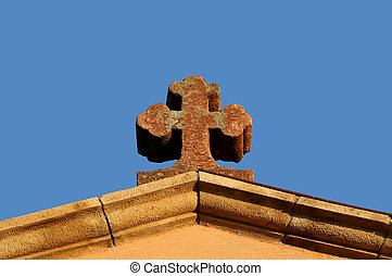 Cross on the curches top with the blue sky in the background...