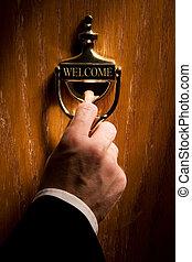 Welcome - Brass door knocker with man\'s hand.