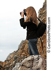 Photographer - Girl taking pictures in the rocky coastline