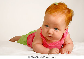 Baby Body - A baby girl lying on her stomach with a pink top...