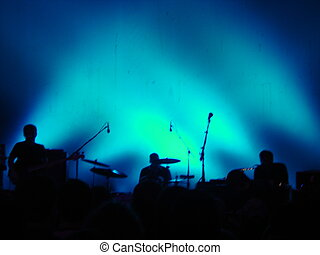 Concert - Silhouettes of a band against a blue background.