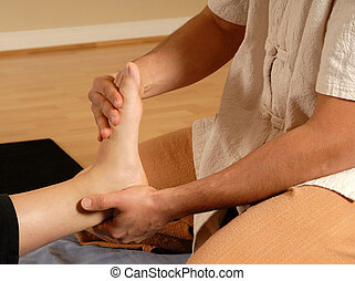 Foot massage - therapist giving a foot massage to client
