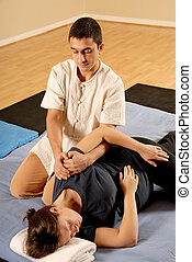 Shoulder stretch - man therapist stretching female client in...