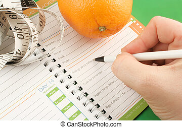 diet journal - writing in a diet and nutrition journal with...