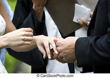 Wedding ceremony ring exchange - Putting the ring on the...
