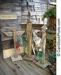 Angels Gather Here - three wooden angels gathered on a barn...