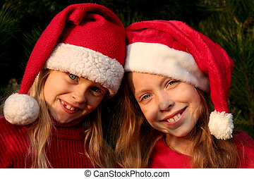 Christmas girls - Portrait of two girls wearing Santa Claus...