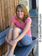Seated Girl - blonde brown eyed teen sitting outside on...