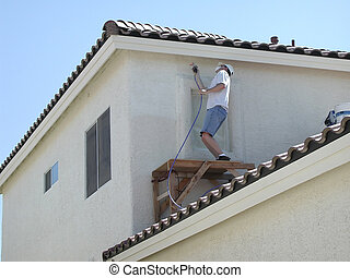 Painter painting a house with a sprayer