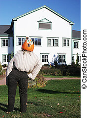 Pumpkin person in front of a house
