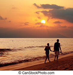 Couple at sunset - Couple walking on the beach at sunset