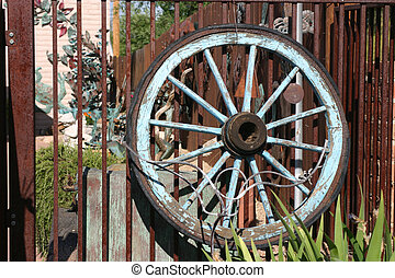 Old Wagon Wheel - Old painted wagon wheel rests against a...