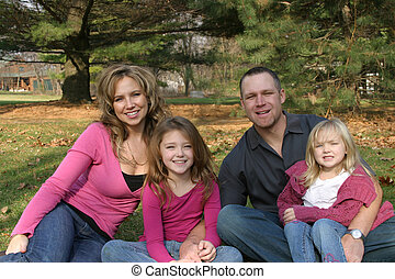 Family Sitdown - mother, father and daughters outside...