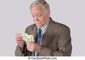 Counting Out His Money - senior mature man in business suit...