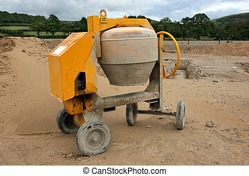 Cement Mixer - Yellow cement mixer on wheels standing idle...