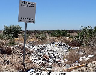 No Dumping - No dumping or trespassing sign next to a pile...