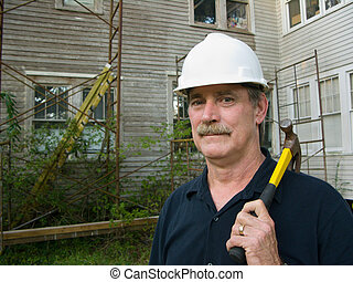 Home Improvement - carpenter with hammer prepares to make...