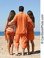 Orange trio - Man and two girls in orange clothes on the...