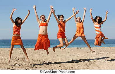 Five girls jumping - Five girls in orange clothes jumping on...