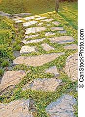 Sunlight path - A sunlit stepping stone path across a lawn