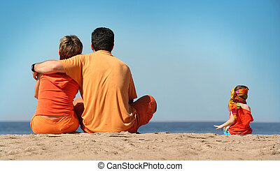Family on the beach - Family in orange clothes on the beach