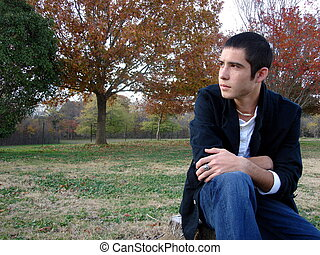 A Young Man Sitting - A yound man sitting on a stump