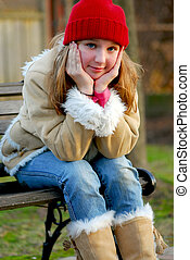 Girl on bench - Portrait of a young girl sitting on a bench...