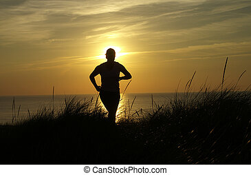 Dunejogger - A woman jogs on dunes in the golden hour sunset...