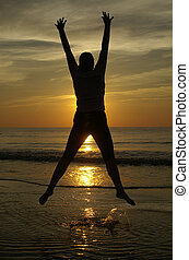 Happy sunset - A happy person jumps up on the beach with the...
