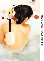 Back of a woman in a foam bath - Young tanned woman with...