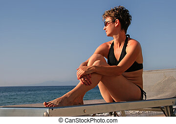 Woman relaxing on a beach looking at the ocean