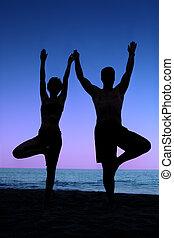 Beach yoga - Couple doing yoga exercise on the beach