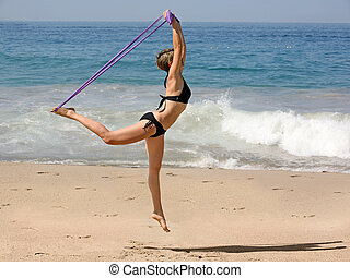 Exercising on the beach - Woman Exercising on the beach with...
