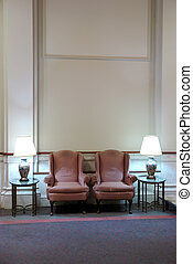 two easy chairs in lobby with high ceiling - two reddish...