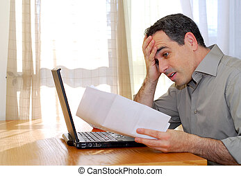 Man with laptop - Man sitting at a desk looking at bills...