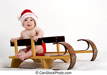 Sleigh ride - Baby boy dressed in red Santa hat, riding on a...