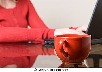 Working at home - Woman in red typing on laptop at home with...