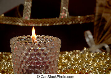 Lit votive candle with gold beads and velvet ribbon in...