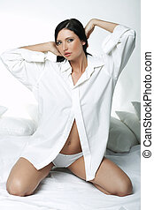 White XXL Shirt - Beautiful brunette woman on bed, wearing...