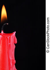 Lit candle - A red candle, lit with wax melting down the...