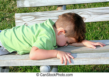 Time For Me - Young boy laying down on a park bench, hiding.