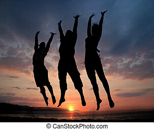 Three people jumping - Three people silhouettes jumping on...