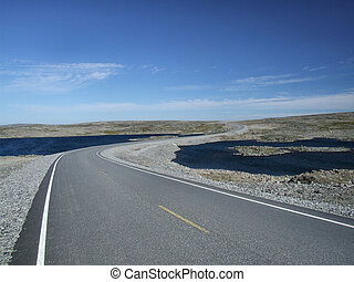 Scenic road among lakes - Norwegian plains landscape. A road...