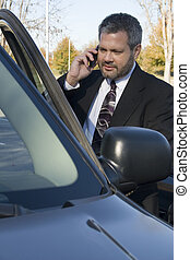 Communication - Business man on cellphone in car.
