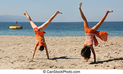 Two girls doing cartwheel - Two girls in orange clothes...