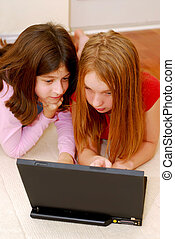 Girls computer - Portrait of two girls lying on the floor...