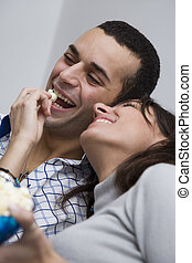 movie night - young couple watching tv at home and laughing