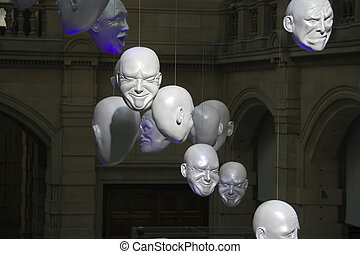 glasgow masks - Sunlit human head sculptures hanging in the...