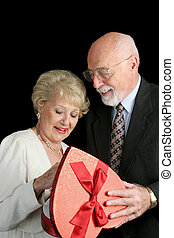 Senior Valentines - A handsome senior man giving a box of...
