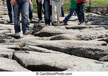 Step by step - Tourist feet at an ancient roman road